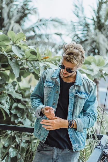 Jovem atraente posando em um local tropical, em um fundo de palmeiras e vegetação Foto gratuita