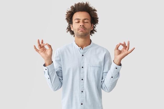 Jovem atraente pratica ioga, sente-se relaxado e calmo, mostra o sinal de mudra com as duas mãos, fecha os olhos tentando se concentrar em algo, posa sozinho contra uma parede branca Foto gratuita