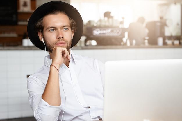 Jovem atraente segurando a mão em seu queixo, olhando pensativo, sentado em frente a um laptop aberto com fones de ouvido e ouvindo um audiolivro online Foto gratuita