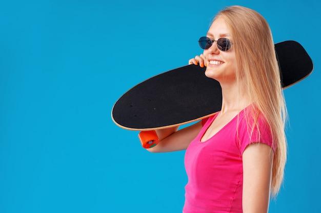Jovem atraente, segurando seu skate sobre azul Foto Premium