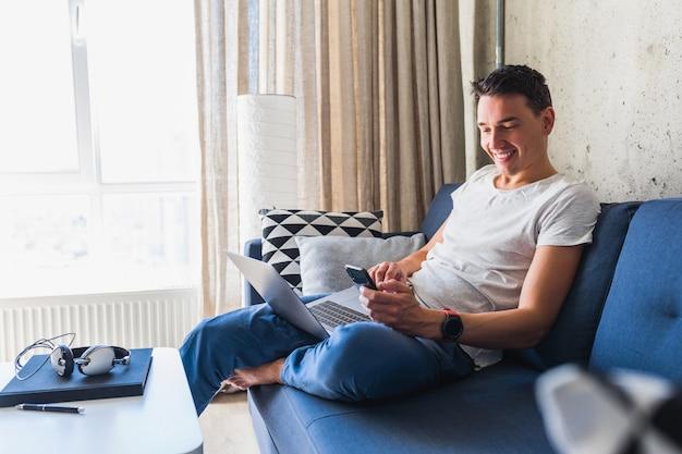 Jovem atraente sentado no sofá em casa segurando um smartphone, trabalhando em um laptop online Foto gratuita