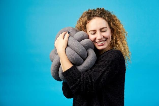 Jovem atraente sorridente alegre gengibre encaracolado abraça um brinquedo macio com prazer. Foto Premium