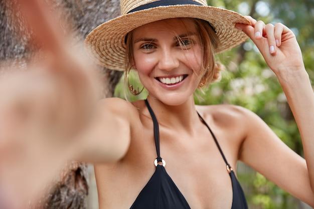 Jovem atraente sorridente viajante feminina de chapéu de palha e biquíni, faz selfie contra um fundo tropical, satisfeita em passar as férias de verão no exterior em um país exótico. conceito de beleza e descanso Foto gratuita