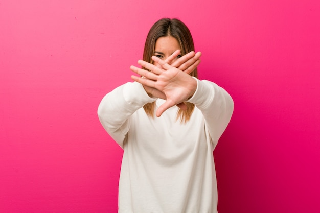 Jovem autêntica mulher carismática contra uma parede, fazendo um gesto de negação Foto Premium
