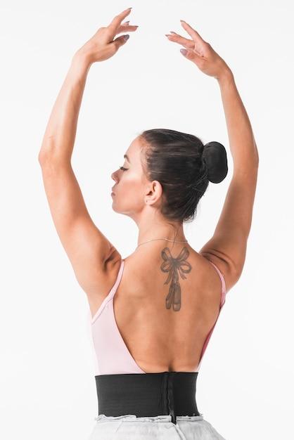 Jovem bailarina com arco e ponta dos pés tatuagem nas costas dela contra o pano de fundo branco Foto gratuita