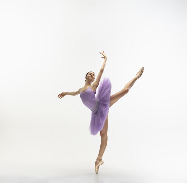 Jovem bailarina concurso graciosa na parede branca Foto gratuita