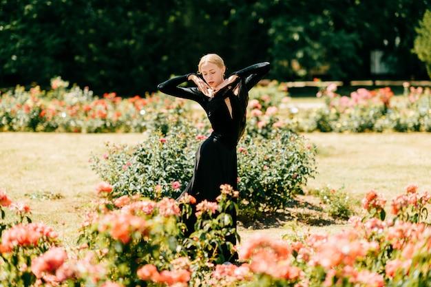 Jovem bailarina de vestido preto, posando e mostrando poses de balé no parque de verão. Foto Premium