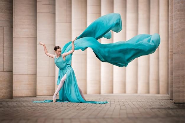 Jovem bailarina em uma pose graciosa em um vestido, se desenvolve como asas entre colunas altas Foto Premium