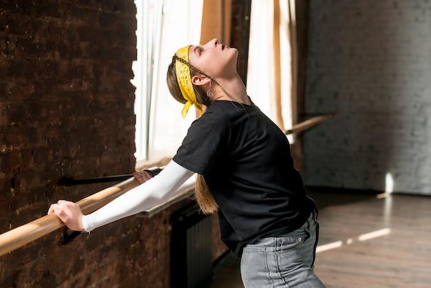 Jovem bailarina feminina, esticando as mãos na barra Foto gratuita