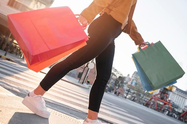 Jovem balançando sacos de compras na rua Foto gratuita