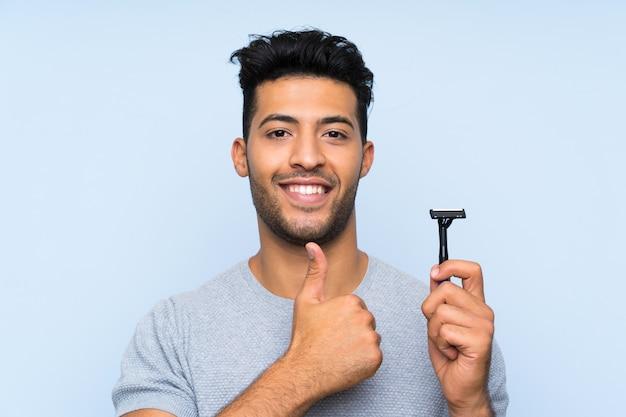 Jovem barbear a barba com o polegar para cima porque algo bom aconteceu Foto Premium