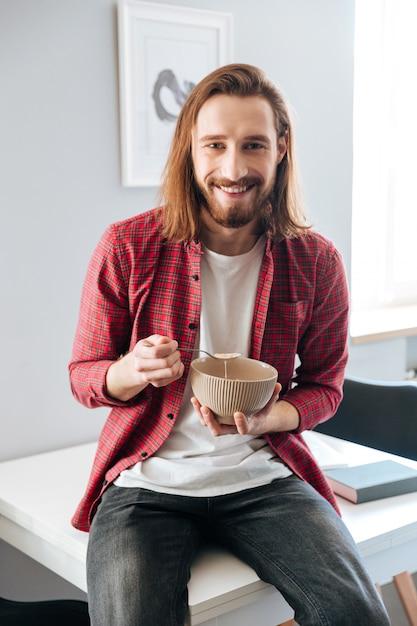 Jovem barbudo alegre tomando café da manhã em casa Foto gratuita