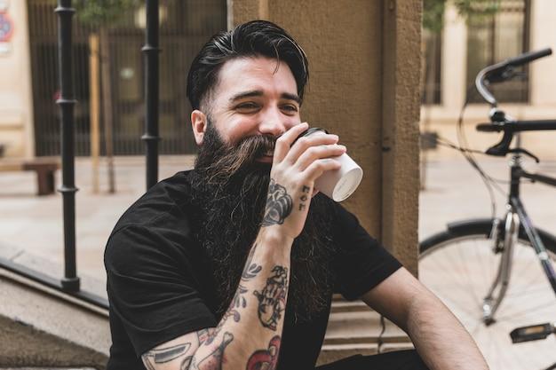Jovem barbudo bebendo o café para viagem Foto gratuita