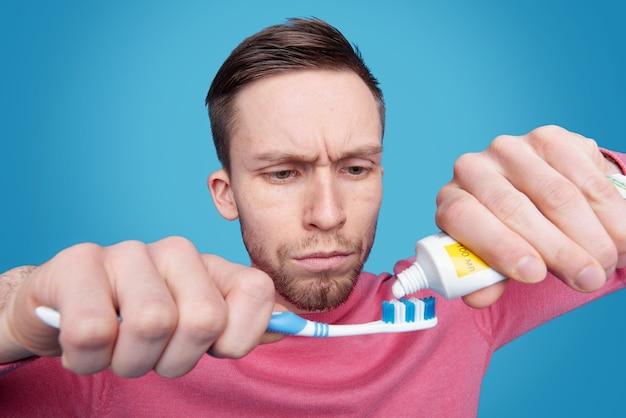 Jovem barbudo concentrado com testa franzida se preparando para escovar os dentes Foto Premium