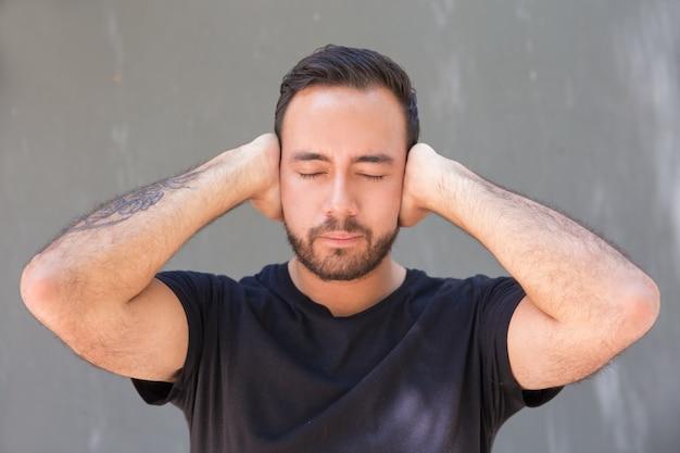 Jovem barbudo, fechando os ouvidos com as mãos Foto gratuita