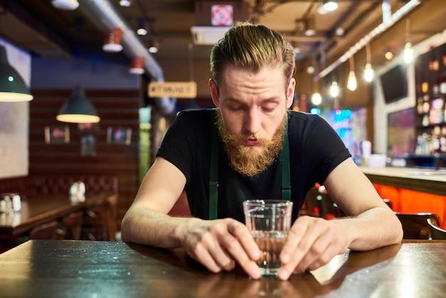 Jovem barbudo, ficando bêbado no bar Foto Premium