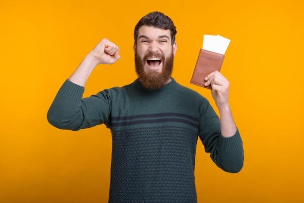 Jovem barbudo ganhou uma viagem para dois está fazendo gesto vencedor, mantendo um passaporte e bilhetes. Foto Premium
