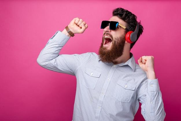 Jovem barbudo homem cantando, dançando e ouvindo a música em fundo rosa. Foto Premium
