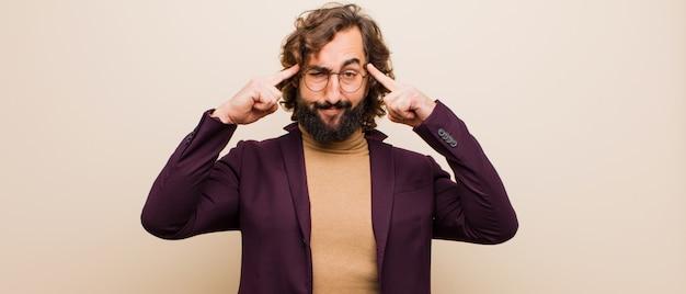 Jovem barbudo homem louco com um olhar sério e concentrado, de brainstorming e pensando em um problema desafiador contra a cor lisa Foto Premium