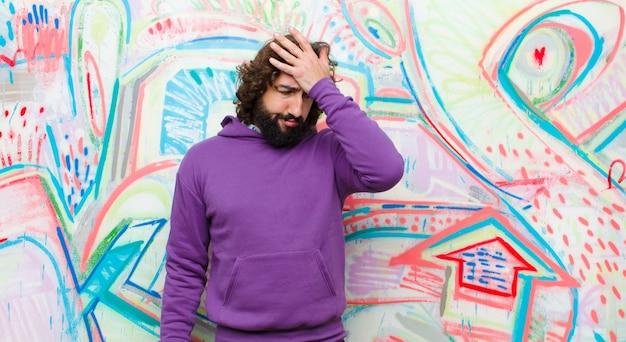 Jovem barbudo homem louco olhando estressado, cansado e frustrado, secando o suor da testa, sentindo-se desesperado e exausto contra a parede de graffiti Foto Premium