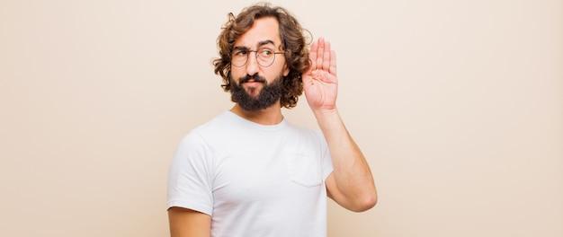 Jovem barbudo homem louco olhando sério e curioso, ouvindo, tentando ouvir uma conversa secreta ou fofoca, bisbilhotando Foto Premium