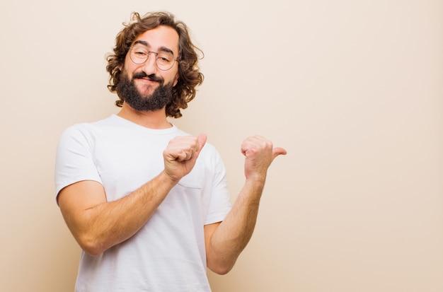 Jovem barbudo homem louco sorrindo alegremente e casualmente apontando para copiar o espaço ao lado, sentindo-se feliz e satisfeito contra a parede de cor lisa Foto Premium