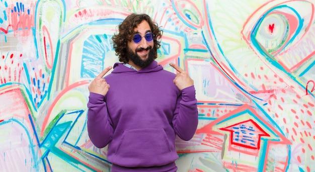 Jovem barbudo homem louco sorrindo confiante apontando para o próprio sorriso largo, atitude positiva, relaxada e satisfeita contra a parede do graffiti Foto Premium
