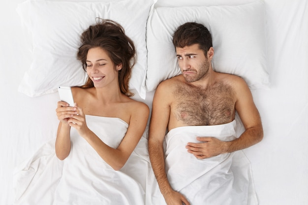 Jovem barbudo infeliz se sentindo triste decepcionado porque a namorada não presta atenção nele Foto gratuita