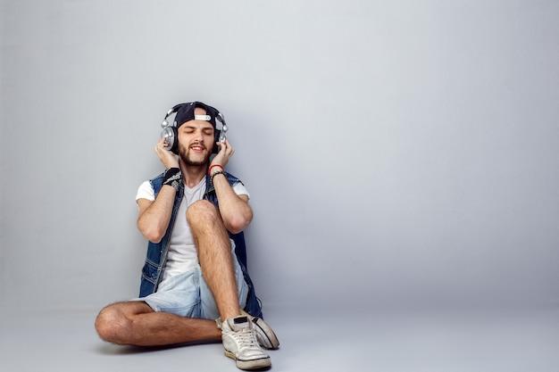 Jovem barbudo relaxado em fones de ouvido Foto Premium