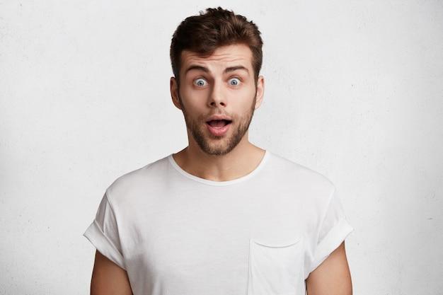 Jovem barbudo surpreso com olhos azuis esbugalhados, vestido com uma camiseta branca casual Foto gratuita