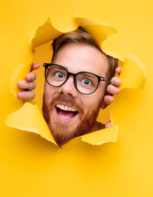 Jovem barbudo surpreso e positivo com óculos espiando de um papel amarelo rasgado Foto Premium