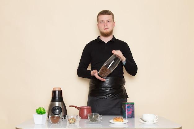 Jovem barista em terno preto com ingredientes e equipamentos de café marrom café sementes em branco Foto gratuita