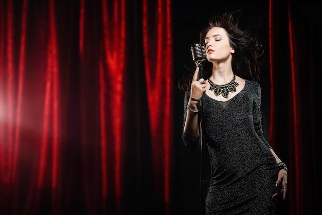Jovem bela cantora de vestido preto com cabelo solto canta no microfone Foto Premium