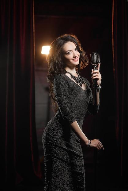 Jovem bela cantora de vestido preto, posando com microfone Foto Premium