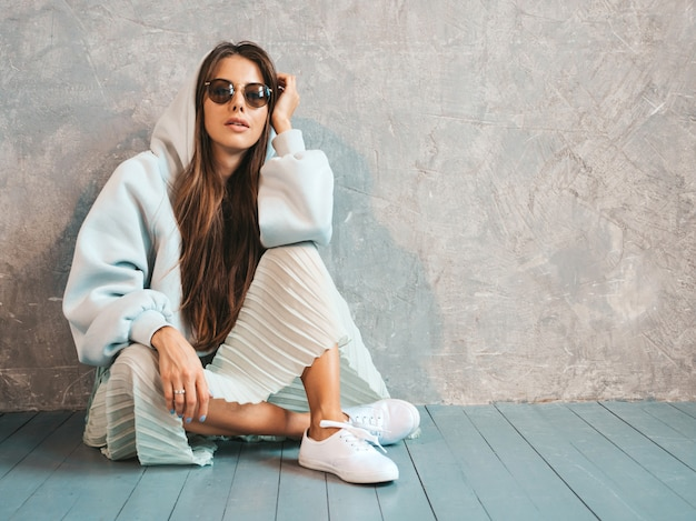 Jovem bela mulher sorridente mostra sinal de paz. menina na moda em roupas de verão casual capuz e saia. sentado no chão Foto gratuita
