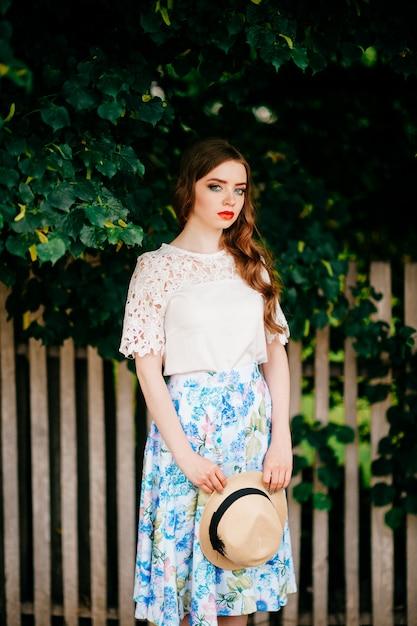Jovem beleza russa. garota atraente em saia longa retrô vintage, top branco antiquado e cabelo ruivo cacheado e chapéu de palha posando para a câmera com cerca e árvores verdes Foto Premium