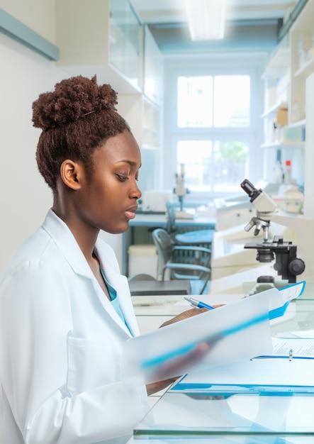 Jovem biólogo feminino africano trabalha no laboratório Foto Premium