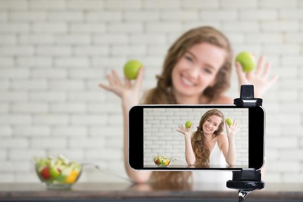 Jovem blogueira e vlogger e influenciadora online transmitem ao vivo um programa de culinária nas mídias sociais usando um smartphone Foto Premium