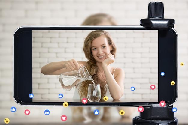 Jovem blogueira, vlogger e influenciadora online transmitem ao vivo um estilo de vida saudável nas mídias sociais usando um smartphone Foto Premium