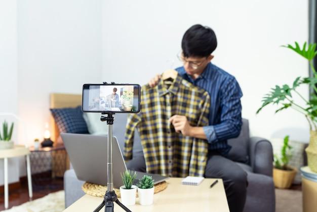Jovem blogueiro asiático gravando vídeo vlog na análise da câmera do produto no escritório em casa, foco na tela da câmera montada no tripé, transmitindo vídeo ao vivo para uma rede social. Foto Premium