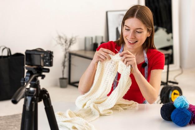Jovem blogueiro tricotando na câmera para os fãs Foto gratuita