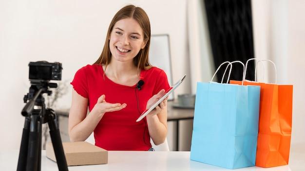 Jovem blogueiro unboxing compras na câmera Foto gratuita