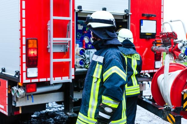 Jovem bombeirouniforme na frente do caminhão de bombeiros Foto Premium