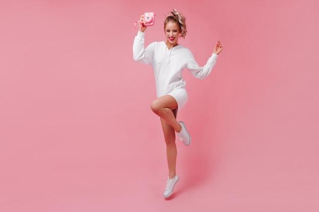 Jovem bonita com vestido esporte posando Foto gratuita