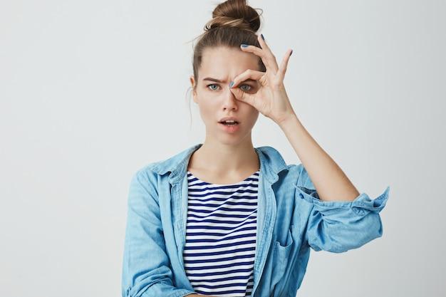 Jovem bonita fazendo gesto de monóculo e olhando por entre os dedos Foto gratuita