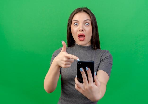 Jovem bonita impressionada segurando e apontando para um telefone celular isolado em um fundo verde com espaço de cópia Foto gratuita
