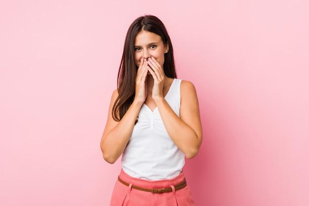 Jovem bonita rindo de algo, cobrindo a boca com as mãos. Foto Premium