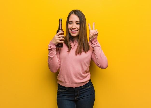 Jovem bonita, segurando uma cerveja, mostrando o número dois Foto Premium