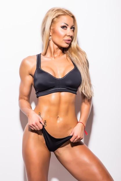 Jovem bonita sexy muscular atlética jovem em traje de banho. biquíni de fitness. corpo magro e musculoso. isolado no branco Foto gratuita