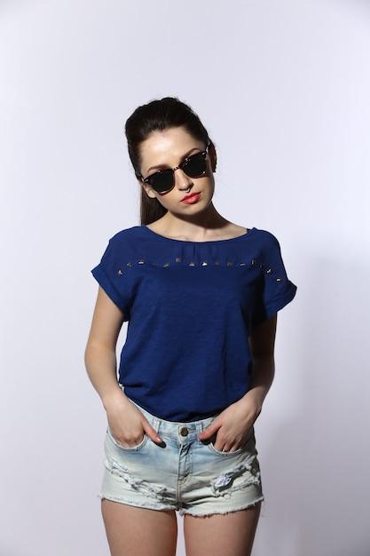 Jovem bonita vestindo jeans e óculos de sol Foto Premium